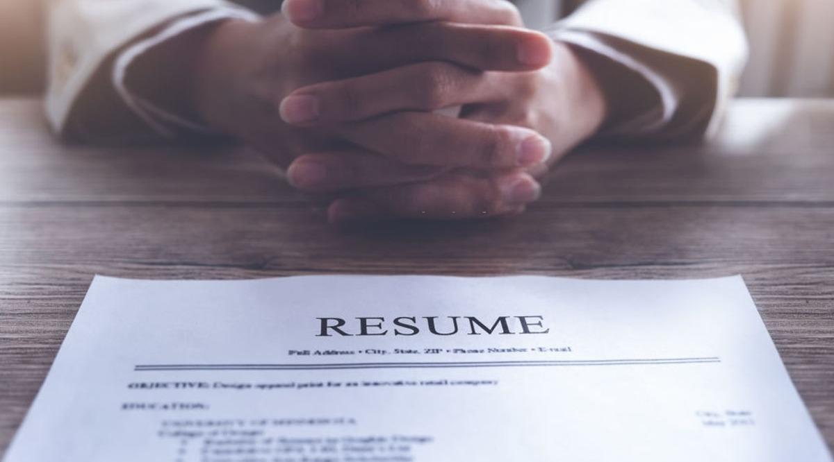 Una persona con un CV en la mesa