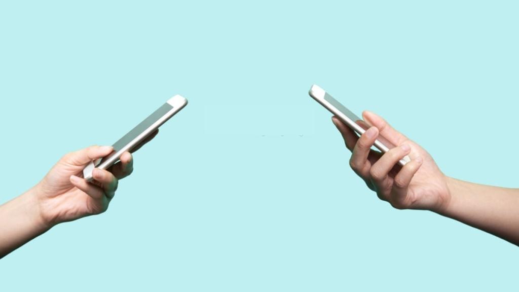 Dos personas con celulares en la mano